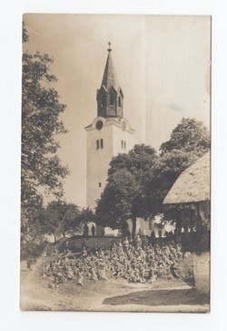 [Untitled] Soldiers sitting in the field in front of a church.
